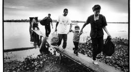 Nicaragua, San Carlos, rio San Juan, februari 2001  Imigranten, illegalen. Nicaraguanen reizen illegaal naar buurland Costa Rica om er te werken. Het dagloon is in Costa Rica ongeveer 5 maal zo hoog als in Nicaragua, vanddar dat naar schatting een miljoen Nicaraguanen (een vijfde deel van de Nicaraguaanse bevolking) in Costa Rica werkt. Naar schaating de helft daarvan verblijft illegaal in het land. De meesten reizen via de plaats San Carlos, vandaar gaan ze met een bootje een paar uur de grensrivier Rio San Juan op om zich ergens af te laten zetten en vandaar Costa Rica in te lopen. Soms duurt die voettocht door het regenwoud en door landbouwgebieden een paar dagen. Als de grenspolitie van Costa Rica illegale migranten aanhoudt, worden ze de grens met Nicaragua weer overgezet.  Migranten vertrekken van de oever van de rio San Juan en lopen costa rica in.  Illegalen. Migratie.  foto Piet den Blanken / Hollandse Hoogte